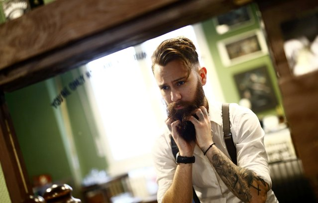 "Alex ""Torreto"" Vellios, a 26-year old barber looks after his own beard as he waits for his first customer of the day at his Torreto barber shop in Frankfurt January 6, 2015. (Photo by Kai Pfaffenbach/Reuters)"