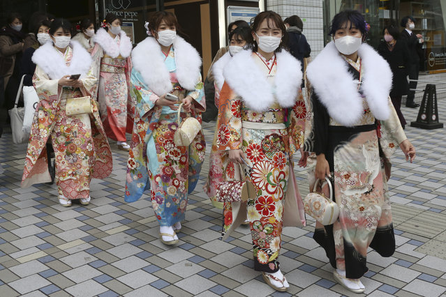 Kimono-clad women wearing face masks to protect against the spread of the coronavirus walk out after a Coming-of-Age ceremony in Yokohama, near Tokyo, Monday, January 11, 2021. (Photo by Koji Sasahara/AP Photo)