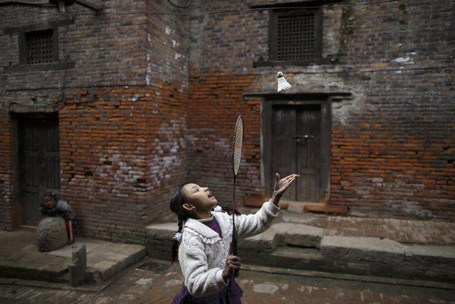 A girl plays badminton along the street outside the old houses of the ancient city of Bhaktapur, near Nepal's capital Kathmandu, January 2, 2015. (Photo by Navesh Chitrakar/Reuters)