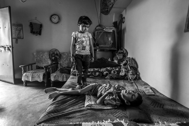 Unnati, 6 years old, at home with his sister Ishika, 4 years old, in the Mahamai Ka Bagh neighborhood. Unnati was born to parents contaminated by a carcinogenic and mutagenic water supply. (Photo by Giles Clarke/Getty Images)