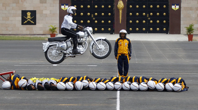 Members of ASC Tornados, the motorcycle display team of the Indian army, lie in a row on the ground as another performs a stunt by jumping over them during the 225th anniversary celebrations of Army Service Corps in Bangalore, India, Tuesday, December 8, 2015. The Army Service Corps which was established in 1790 is an arm of the Indian Army which handles its logistic support function. (Photo by Aijaz Rahi/AP Photo)