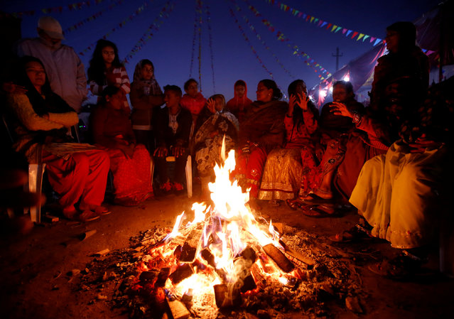 """Devotees gather around a fire as they wait to offer prayer to the rising sun during the """"Chhat"""" festival along the bank of Bagmati River in Kathmandu, Nepal November 7, 2016. (Photo by Navesh Chitrakar/Reuters)"""