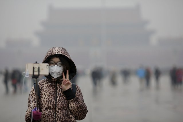 "A woman wearing a protective mask has her picture taken just after a flag-raising ceremony amid heavy smog at the Tiananmen Square, after the city issued its first ever ""red alert"" for air pollution, in Beijing December 9, 2015. (Photo by Damir Sagolj/Reuters)"