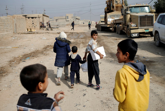 Children carry a food given by Iraqi soldiers in a village outside Mosul, Iraq November 9, 2016. (Photo by Goran Tomasevic/Reuters)