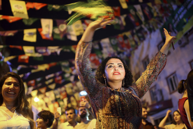 Women dance under election banners of the pro-Kurdish Peoples' Democratic Party, or HDP, in the mainly-Kurdish city of Diyarbakir, southeastern Turkey, Sunday, June 24, 2018. Partial results show the pro-Kurdish party has passed a critical electoral threshold to enter the Turkish parliament, risking the ruling party's majority. (Photo by Emre Tazegul/AP Photo)