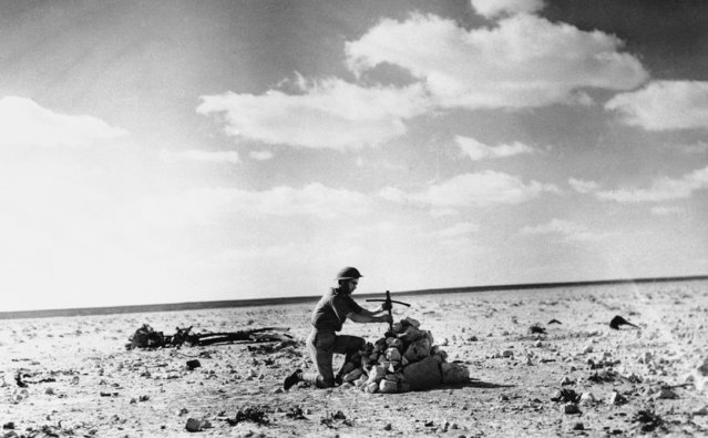 British sources describe this as a RAF Airman placing a cross, made from the wreckage of their Aircraft, over a grave on December 27, 1940, of five Italian Airmen shot down in the Desert Battle at Mersa Matruh on October 31. (Photo by AP Photo)