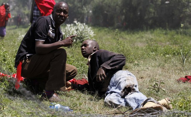 A resident attempts to assist a man shot and injured during protests to oust Narok county Governor Samuel Tunai in Narok, Kenya, January 26, 2015. (Photo by Thomas Mukoya/Reuters)