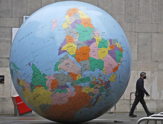 """A man wearing a face mask walks past a globe in front of the London School of Economics in London, Tuesday, January 19, 2021. The globe designed by Mark Wallinger is called """"The World turned Upside Down"""". The U.K. is under an indefinite national lockdown to curb the spread of the new variant, with nonessential shops, gyms and hairdressers closed, most people working from home and schools largely offering remote learning. (Photo by Frank Augstein/AP Photo)"""