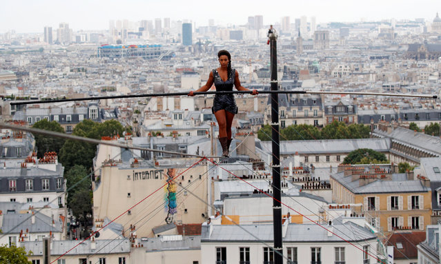 Tightrope walker Tatian-Mosio Bongonga advances on a tightrope as she scales the Monmartre hill towards the Sacre Coeur Basilica (not pictured) in Paris, France, July 20, 2018. (Photo by Philippe Wojazer/Reuters)