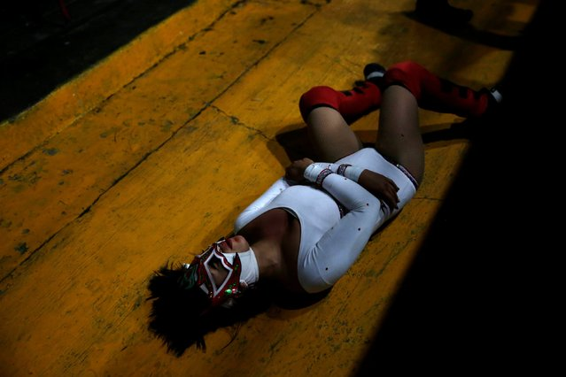 Zuzu Divine lies down on the floor during a wrestling fight at Arena Neza on the outskirts of Mexico City, Mexico October 28, 2016. (Photo by Carlos Jasso/Reuters)