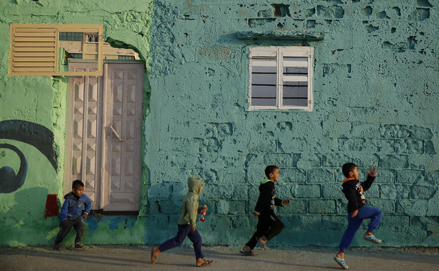 In this Saturday December 19, 2015 file photo, Palestinian boys run by a painted house in the Shati Refugee Camp in Gaza City. Shati has always been a symbol of poverty, a grey concrete jungle with 87,000 people packed into one fifth of a square mile (half a square kilometer). But now, overlooking the sewage-contaminated Mediterranean beachfront, the camp's houses are covered in vibrant colors. (Photo by Hatem Moussa/AP Photo)