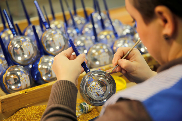 """An employee paints a glass Christmas and New Year decoration at the """"Yolochka"""" (Christmas tree) factory, which has been producing glass decorations and toys for the festive season since 1848, in the town of Klin outside Moscow, Russia, November 24, 2016. (Photo by Maxim Zmeyev/Reuters)"""