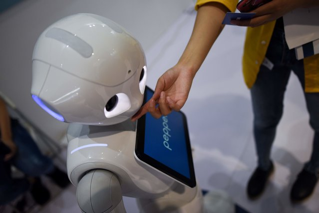 A woman touches a robot at the 2018 World Robot Conference in Beijing on August 15, 2018. (Photo by Wang Zhao/AFP Photo)