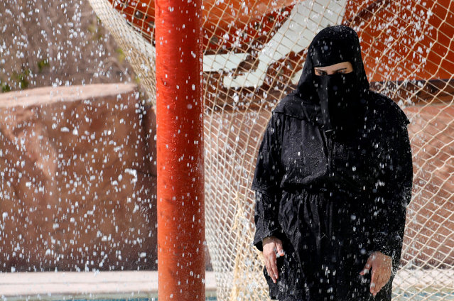 A woman wearing a full veil (niqab) uses a shower to cool off in hot and humid weather inside an Aqua arena during summer holidays at El Ain El Sokhna in Suez, east of Cairo, Egypt July 21, 2018. (Photo by Amr Abdallah Dalsh/Reuters)