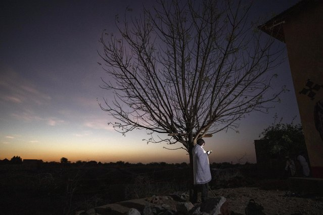 A Tigrayan refugee man looks at his mobile phone in front of a church near Hamdeyat Transition Center near the Sudan-Ethiopia border, eastern Sudan, March 21, 2021. (Photo by Nariman El-Mofty/AP Photo)