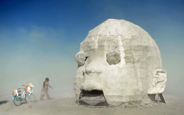 """Sam Ray visits the """"Baby Head"""" art piece at Burning Man in Gerlach, Nevada. (Photo by Andy Barron/The Reno Gazette-Journal)"""