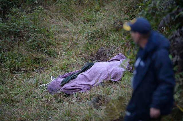 A rescuer walks past the body of a victim from the LAMIA airlines charter plane crash in the mountains of Cerro Gordo, municipality of La Union, on November 29, 2016. (Photo by Raul Arboleda/AFP Photo)