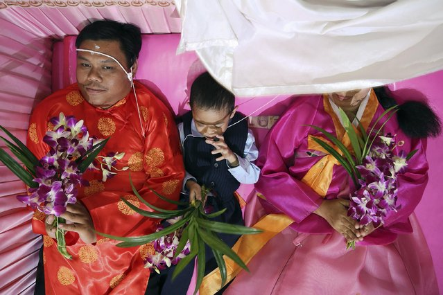 Sibb, 3, holds flowers between between his parents laying inside a pink coffin during their wedding ceremony at Wat Takien temple in Nonthaburi province, on the outskirts of Bangkok February 14, 2015. (Photo by Damir Sagolj/Reuters)