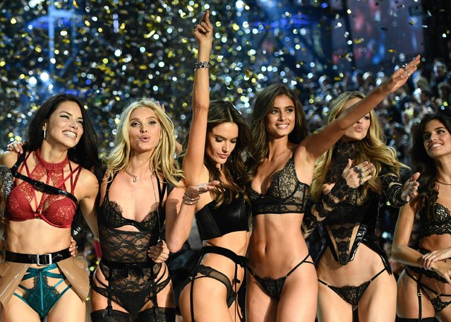 Victoria's Secret Angels (fromL) Brazilian model Adriana Lima, Swedish model Elsa Hosk, Brazilian model Alessandra Ambrosio, US model Taylor Hill, US model Martha Hunt and Portuguese model Sara Sampaio cheer during the 2016 Victoria's Secret Fashion Show at the Grand Palais in Paris on November 30, 2016. (Photo by Martin Bureau/AFP Photo)