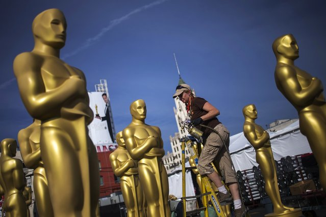 Dena D'Angelo, a scenic artist, prepares to spray Oscar statues in a parking lot near the Dolby Theatre in Hollywood, ahead of the Academy Awards in Los Angeles, California February 18, 2015. The 87th Academy Awards ceremony, which honors the best films of 2014, will take place Sunday at the Dolby Theatre in Hollywood. (Photo by Adrees Latif/Reuters)
