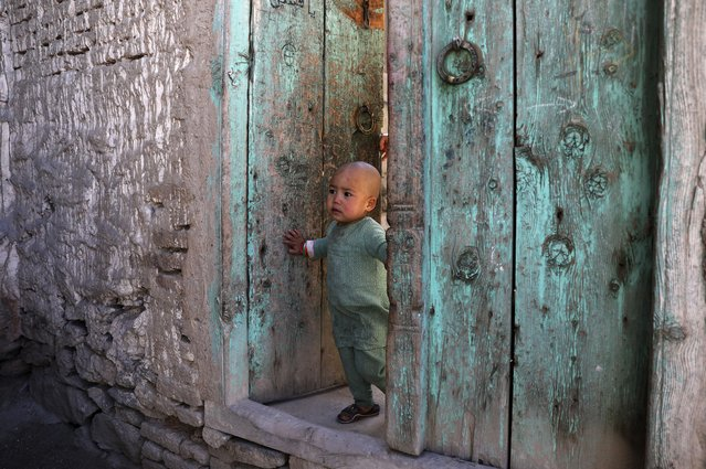 An Afghan girl stand in the doorway of her home in Kabul, Afghanistan, Monday, March 29, 2021. (Photo by Rahmat Gul/AP Photo)