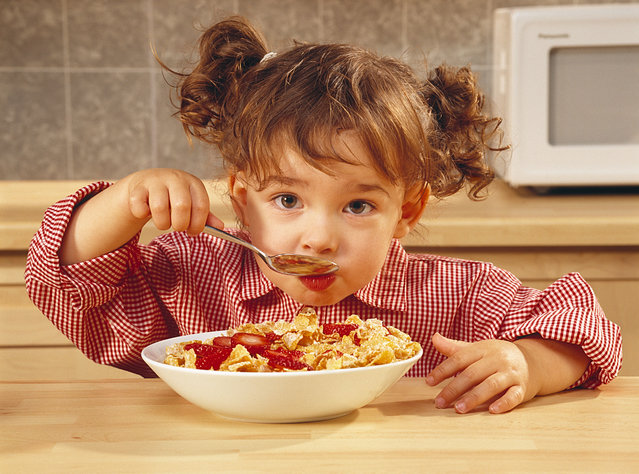 Girl eating bowl of cereal with strawberries. (Photo by Matthew Plexman/Alamy Stok Photos)