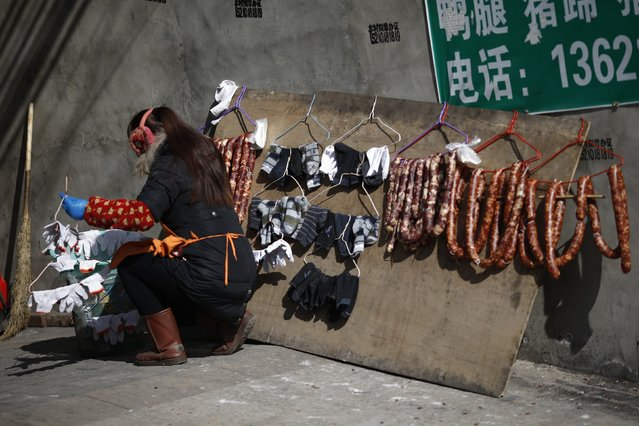 A woman hangs laundry next to sausages, that have been left out to dry, at a migrant workers' village in Beijing February 12, 2015. (Photo by Kim Kyung-Hoon/Reuters)