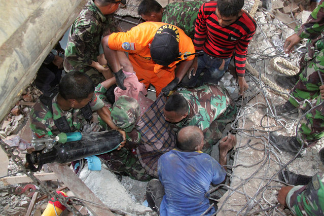 Indonesian rescue workers carry a survivor from a fallen building after an earthquake in Trienggadeng, Pidie Jaya, in the northern province of Aceh, Indonesia December 7, 2016. (Photo by Reuters/Antara Foto/Ampelsa)