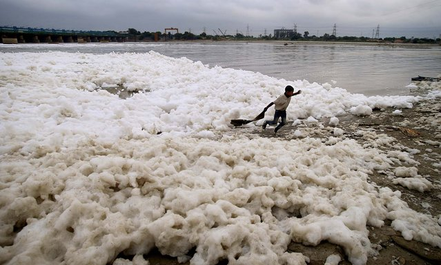 A young boy runs in the polluted water of the river Yamuna in New Delhi, on October 4, 2013. Although only 22 kilometers of the river passes through New Delhi, the city contributes to over 50 percent of the pollution by discharging sewage through several drains that empty into the river. (Photo by Saurabh Das/Associated Press)