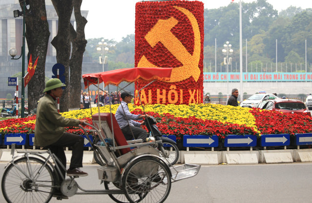 In this Tuesday, January 19, 2016, photo, vehicles drive past a sign marking the 12th Congress of the Communist Party of Vietnam in Hanoi, Vietnam. This week, some 1,510 representatives of Vietnam's Communist party gather in the capital to pick the country's new leaders. (Photo by Hau Dinh/AP Photo)