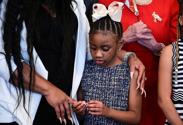 Gianna Floyd, George Floyd's daughter, holds the hand of her mother, Roxie Washington, while standing with members of the Floyd family prior to a meeting to commemorate the death of George Floyd with U.S. House Speaker Nancy Pelosi (D-CA) at the U.S. Capitol in Washington, U.S., May 25, 2021. (Photo by Erin Scott/Pool via Reuters)
