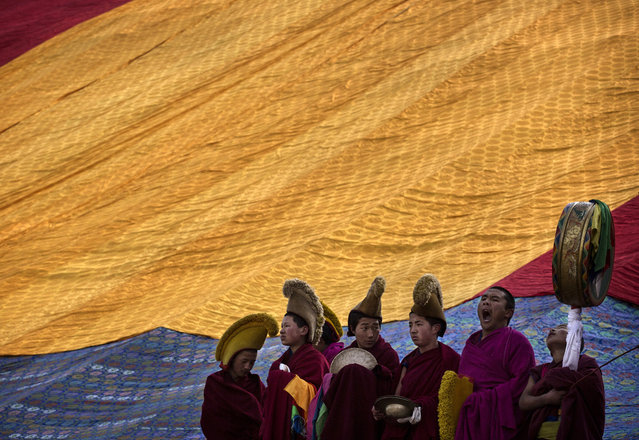 Tibetan Buddhist Monks of the Gelug, or Yellow Hat order, stand in front of a covered large thangka showing Buddha before unveiling it during Monlam or the Great Prayer rituals on March 3, 2015 at the Labrang Monastery, Xiahe County, Amdo, Tibetan Autonomous Prefecture, Gansu Province, China. (Photo by Kevin Frayer/Getty Images)