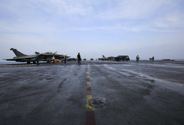 French sailors work on the flight deck of the French Navy aircraft carrier Charles de Gaulle Wednesday, March 18, 2015, in the Persian Gulf. (Photo by Hasan Jamali/AP Photo)
