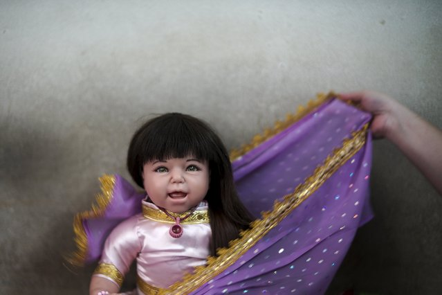 "A devotee dresses up her ""child angel"" doll near Wat Bua Khwan temple in Nonthaburi, Thailand, January 26, 2016. (Photo by Athit Perawongmetha/Reuters)"