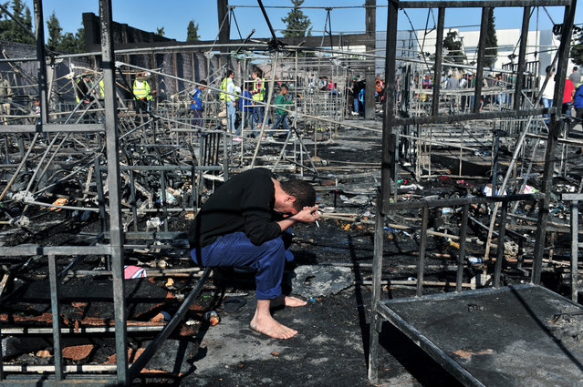A man holds his head in his hands as he sits among bed frames burned by a fire which tore through a refugee camp in Diavata, northern Greece, on April 20, 2016, threatening the lives of over 2,300 people who live there. More than a dozen tents were destroyed in the blaze. Police said at least two people were taken to a hospital suffering from smoke inhalation. (Photo by Sakis Mitrolidis/AFP Photo)