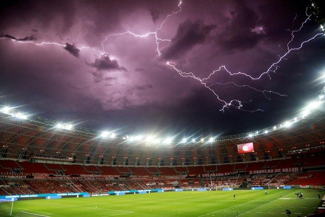 Lightning streaks across the sky before the Copa Libertadores Round of 16 match between Internacional and Boca Juniors at Beira Rio Stadium in Porto Alegre, Brazil on December 2, 2020. (Photo by Silvio Avila/Pool via Reuters)