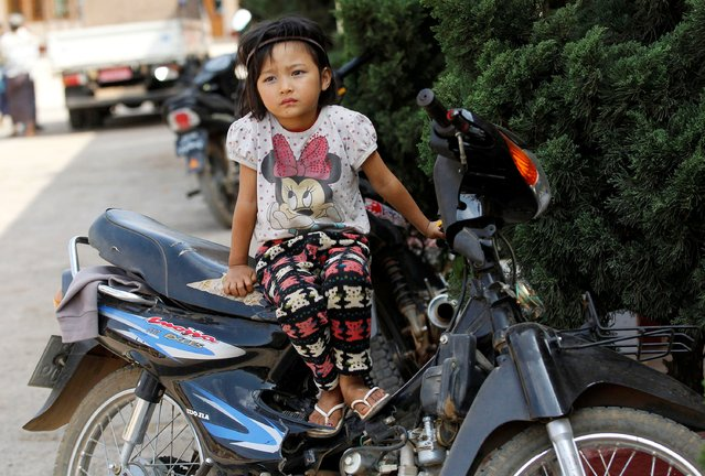 Nann Mie Mie, 4-years-old,  sits on motorbike at temporary refugee camp at a monastery in Lashio February 20, 2015. (Photo by Soe Zeya Tun/Reuters)