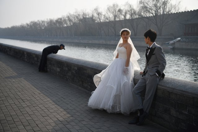 A couple poses for wedding photos beside the moat which surrounds the Forbidden City in Beijing on February 26, 2021. (Photo by Greg Baker/AFP Photo)