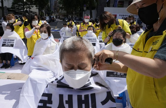 Workers wearing face masks to help protect against the spread of the coronavirus shave their heads during a rally demanding job security in Seoul, South Korea, Wednesday, June 16, 2021. (Photo by Ahn Young-joon/AP Photo)