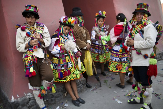 In this Sunday, March 29, 2015 photo, dancers from the La Mar district of Ayacucho, dressed in their traditional costumes, wait to perform in the Vencedores de Ayacucho dance festival, in the Acho bullring in Lima, Peru. The festival does not focus on the typical dances of Peru's highlands, but contain macabre reminders of the bitter conflict that the people from the Ayacucho region, or their parents, had endured. (Photo by Rodrigo Abd/AP Photo)