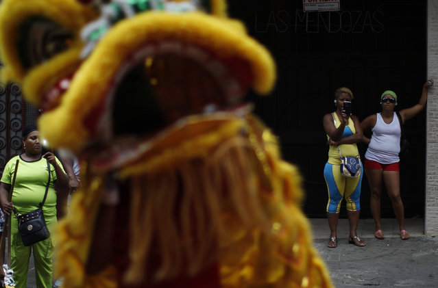 Bystanders watch as dancers perform a lion dance outside a local shop during celebrations of the Chinese Lunar New Year of the Monkey in Chinatown in Panama City, Panama February 8, 2016. (Photo by Carlos Jasso/Reuters)