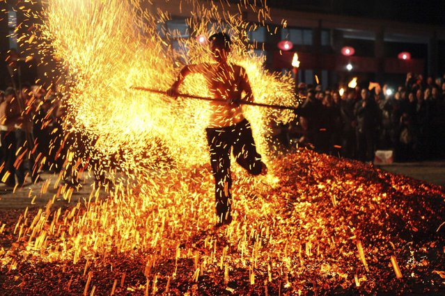 "A man sweeps burning charcoal as he participates in the traditional ritual called ""Lianhuo"", or ""fire walking"", in Pan'an county, China, on November 25, 2013. Lianhuo, a traditional local ritual which was listed in 2005 as an intangible cultural heritage of the province, usually requires dozens of men to walk past burning charcoal or firewood barefooted, as a way to ward off evil and pray for good fortune. (Photo by Reuters/Stringer)"