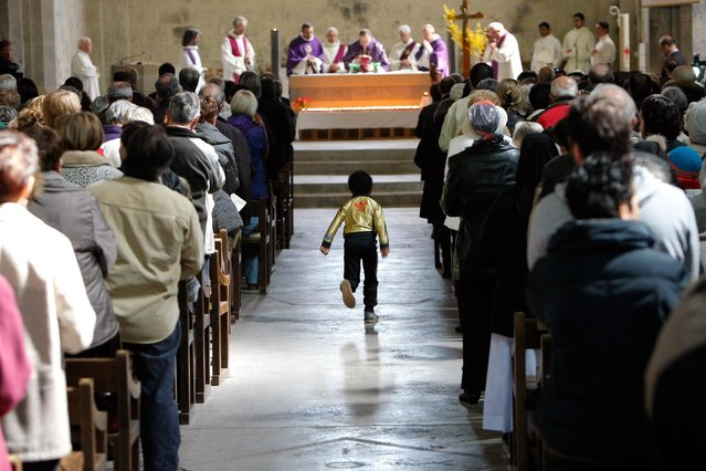 A child runs along the aisle during a special Mass to honour the victims of the Germanwings jet crash, inside the cathedral Notre Dame de Bourg, in Digne-les-Bains, France, Saturday, March 28, 2015. (Photo by Claude Paris/AP Photo)