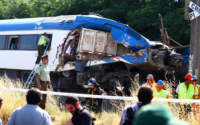 Rescuers work on the wreckage of a passenger train that collided with a truck near Requinoa, some 100km south of Santiago, on December 4, 2013, leaving at least two persons dead and eight wounded. (Photo by Danny Bolivar/AFP Photo)