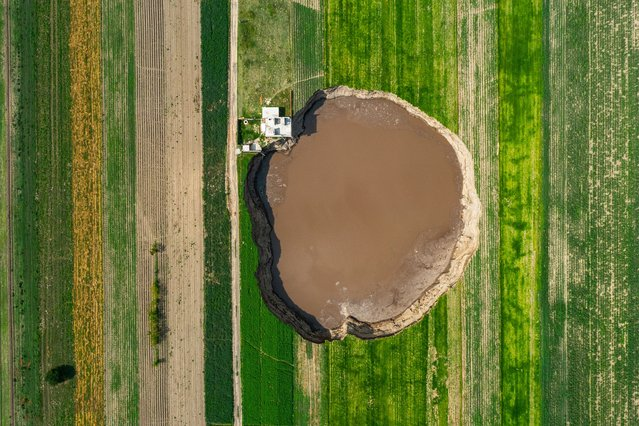 Aerial view of a giant sinkhole on June 09, 2021 in Santa María Zacatepec, Mexico. The giant sinkhole is located 20 kilometers northwest from the capital city Puebla, the hole now measures 110 meters across its widest point, covering around 11,000 square meters and damaging a house built near the place where it appeared. Farmers of the surroundings have been affected since they are not allowed to enter their fields due to the warning perimeter set up by the authorities. (Photo by Hector Vivas/Getty Images)