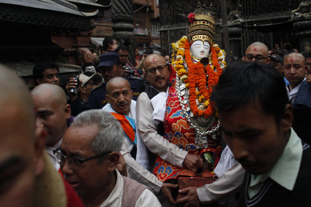 A Priest carries the idol of Seto Machindranath to place inside a chariot which will then be pulled, during the Seto Machindranath Chariot festival in Kathmandu, Nepal, Friday, March 27, 2015. (Photo by Niranjan Shrestha/AP Photo)