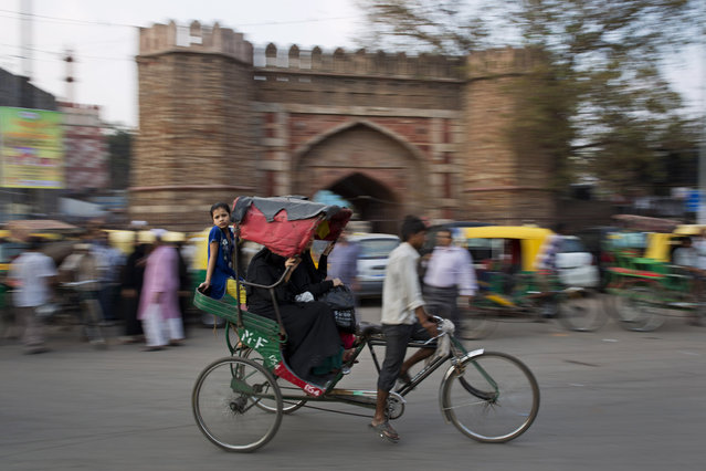 An Indian girl balances herself on the edge of a rickshaw moving past the historic Turkman Gate in the old Delhi area of New Delhi, India, Tuesday, April 14, 2015. The four-century-old neighborhood is chaotic and crowded, yet is the vibrant heart of the city. (Photo by Bernat Armangue/AP Photo)