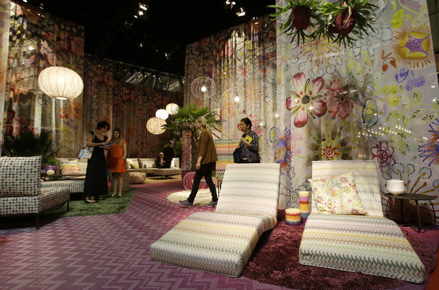 In this picture taken on Tuesday, April 14, 2015, people walk past creations by Missoni Home at the Milan Furniture Fair, in Milan, Italy. A Memphis Group revival permeated this year's Milan Furniture Fair, and it wasn't just the appearance of acid colors and fanciful squiggles that helped characterize the 1980s post-futuristic design movement launched here, but a pervasive search for clarity. (Photo by Antonio Calanni/AP Photo)