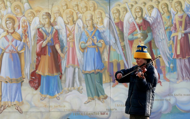 A young woman plays violin to collect money in front of Mikhailovsky Cathedral frescos in downtown Kiev, Ukraine, 17 January 2017. The National Bank of Ukraine planned to sell up to 100 million US Dollar to the Ukrainian banks in the foreign exchange auction on 17 January to saving Hryvnia quotations against the dollar on the interbank currency market. (Photo by Sergey Dolzhenko/EPA)