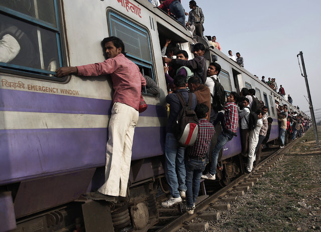 Passengers travel on an overcrowded train on the outskirts of New Delhi, February 26, 2015. (Photo by Ahmad Masood/Reuters)